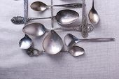 Metal spoons on fabric background