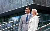 business, partnership, success and people concept - smiling businessman and businesswoman standing over office building