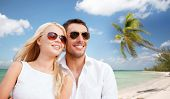 summer holidays, travel, tourism, people and dating concept - happy couple in shades over tropical beach background