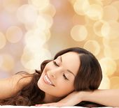 beauty, people and health concept - beautiful young woman lying with closed eyes over beige lights background