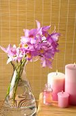 branch orchid in glass with oil, candle on the bamboo background