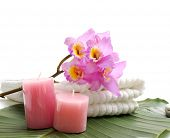 Branch pink orchid on towel and candle on banana leaf