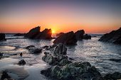 Sunset Over Rocks On Sharrow Beach Part Of Whitsand Bay In Cornwall