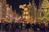 WROCLAW, POLAND - DECEMBER 21: Residents and tourists visit the Christmas market in the Old Market Square in front of City Hall on 21 December 2014 in Wroclaw, Poland.