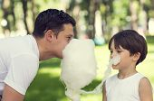 father and son eating cotton candy