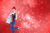 Festive blonde holding shopping bags against digitally generated delicate snowflake design