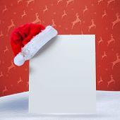 Santa hat on poster against orange reindeer pattern