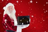 Santa Claus presents a laptop against red snowflake background