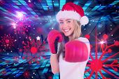 Festive blonde punching with boxing gloves against digitally generated cool disco design