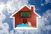 Couple sitting on couch watching a television at home against bright blue sky with clouds