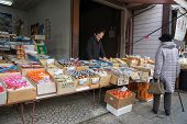TAKAYAMA, JAPAN - DECEMBER 3, 2014: Local shopping at the Miyagawa morning market in Takayama, Japan. This morning market sells food items, groceries to farm produce and is common in rural Japan.