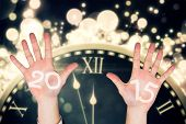 Hands against black and gold new year graphic