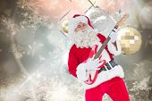 Smiling santa playing electric guitar against hanging christmas decorations