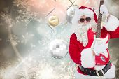 Santa with sunglasses playing electric guitar against hanging christmas decorations