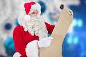 Santa checking list against christmas decorations hanging from branch