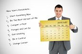Businessman pointing at calendar he is holding against yellow card