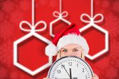 Festive blonde holding a clock against blurred christmas background