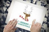 Merry Christmas message against hands touching tablet screen