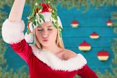 Festive cute blonde holding mistletoe against blurred christmas decorations hanging over wood