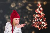 Festive blonde blowing over hands against shimmering christmas tree of lights