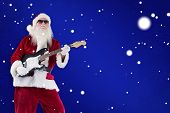 Santa Claus plays guitar with sunglasses against blue snowflake background