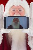 Santa records himself with a smartphone against red background