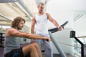 Side view of a male trainer assisting young man on fitness machine at the gym