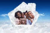 Happy family posing on the couch together against bright blue sky over clouds