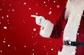 Santa Claus points at something against red snowflake background