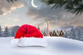 Santa hat on snow against cute christmas village at north pole