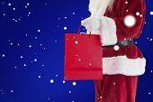 Santa carries red gift bag against blue