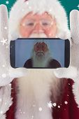 Santa records himself with a smartphone against green snowflake background