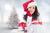 Unsure brunette in santa hat packing gifts against blurry christmas tree in room