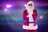Santa Claus wears black sunglasses against digitally generated cool disco background
