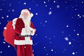 Santa carries his red bag against blue snowflake background
