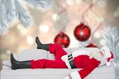 Santa claus sleeping on the couch against digital hanging christmas bauble decoration