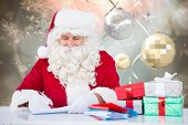 Santa writing cards against hanging christmas decorations
