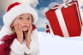 Cute little girl wearing santa hat and tinsel against blue sky with white clouds