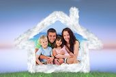 Portrait of a family at the beach against green grass under blue and purple sky