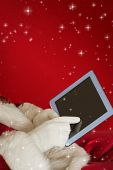 Santa using tablet on the armchair against red snowflake background