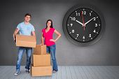 Young couple with moving boxes against grey room