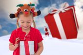 Cute little girl wearing rudolph headband against blue sky with white clouds
