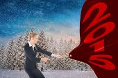 Focused blonde businesswoman pulling a rope against snowy landscape with fir trees