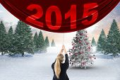 Businesswoman pulling a chain against christmas tree in snowy landscape