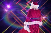 Santa carrying sack of gifts against digitally generated disco laser background