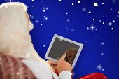 Rear view of santa using tablet on the armchair against blue snowflake background