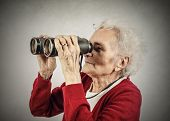 Elderly woman using binoculars