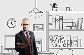 Young confident businessman standing in drawn office