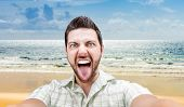 Happy young man taking a selfie photo on the beach