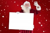 Santa holds a sign and is waving against red snowflake background
